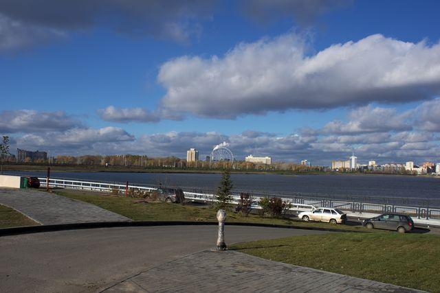 Городской пейзаж: асфальт, вода, здания, каскады облаков